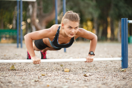 Workout Exercise. Handsome Determined Active Woman With Fit Muscular Body Doing Push Ups Exercises. Sporty Athletic Female Doing Plank At Park, Training Outdoor. Sports And Fitness Concept.