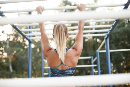 Back view of fit tanned woman training outdoors on monkey bars. Athletic woman using outdoor exercise equipment for sports training.