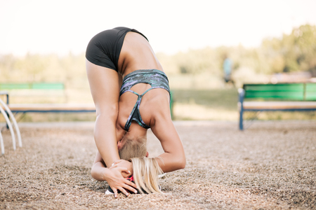 Fit tanned woman model doing stretching leaning to her legs with her body on the park sport ground. Athletic woman using outdoor exercise  for sports training. Healthy life style.