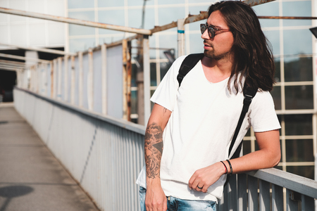 Stylish hipster model with long hair lifestyle in the street. Dressed in a white T-shirt and torn blue jeans in the city Stock fotó