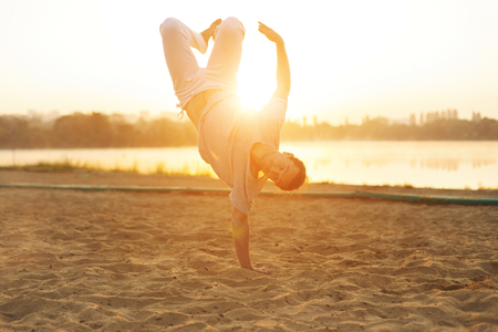 Concept about people, lifestyle, sport. Capoeira on the beach, near lake in the park one performer, at sunrise. Casual athletic man in white pants upside down, jumping with legs in air while workout.