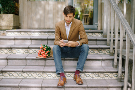 Handsome man texting while looking at the phone Stock Photo