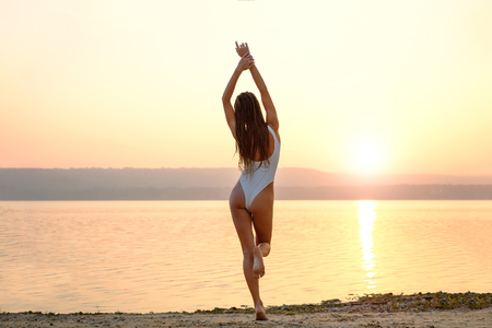 woman bath: Young woman in strings swimsuit stands on the beach in sunrise Stock Photo