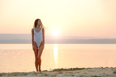 Young woman in strings swimsuit stands on the beach in sunrise Standard-Bild
