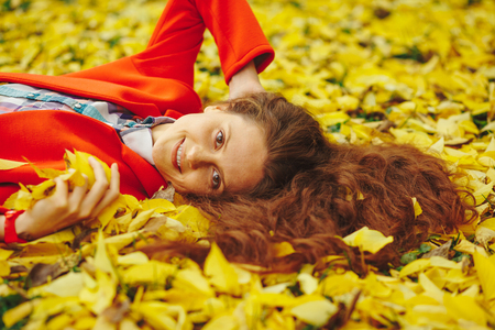 Young beautiful lady surrounded autumn leaves 版權商用圖片