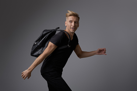 Handsome young man running with a backpack on shoulders Archivio Fotografico