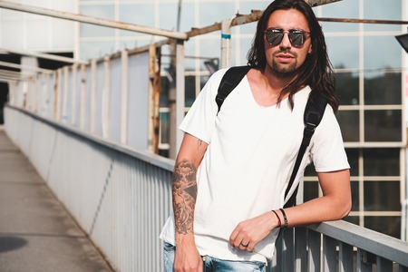 Young attractive bearded man with tattoos and long hair wearing sunglasses, white shirt and backpack posing on urban background
