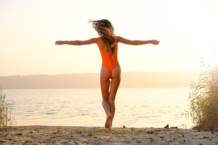 Attractive girl in swimsuit on the beach at sunrise Standard-Bild