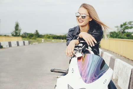 Smiling attractive young woman posing on a motorbike wearing fashionable sunglasses, leather jacket, stylish haircut. Confident face expression, hairstyle, sensual biker female