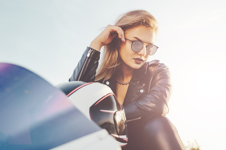 Close-up portrait young beautiful biker in fashionable sunglasses and leather clothes touching eyewear and hair with hand. Attractive female portrait. Dream woman. Glasses model posing. Banco de Imagens