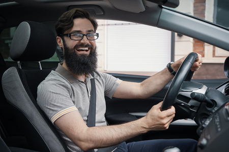 Happy charismatic man driving a car