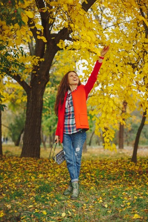 Happy girl with long wavy hair enjoying autumn in the park. Beautiful young woman touching leaves on the trees in the autumn park.