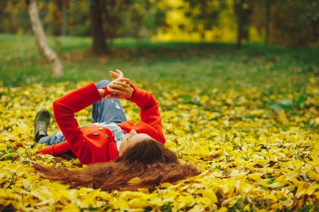 Smiling girl with long wavy hair enjoing life in autumn forest. Cheerful beautiful girl in red cout and colorful plaid shirt on beautiful fall day. Beautiful happy girl laying in yellow autumn leaves. 版權商用圖片