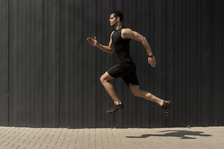 A side view shot of a fit young, athletic man jumping and running, doing cardio interval training against a grey background. Fitness male exercising, outdoors in the morning.