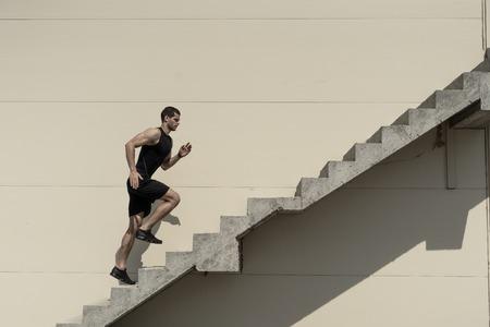 Fino in cima, superando le sfide. Forte uomo atletico salire le scale