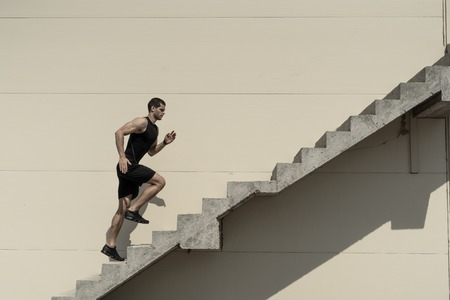 Up to top, overcoming challenges. Strong athletic man climbing stairs