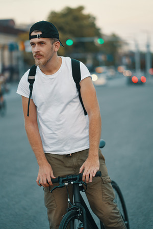 Portrait of a young man riding on bicycle in the city road, street with city far in the background. Male on black bicycle with white shirt, cap, backpack cycling to destination Фото со стока