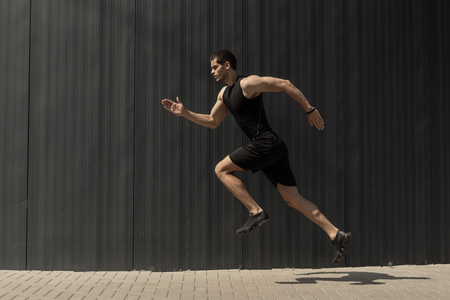 A side view shot of a fit young, athletic man jumping and running doing cardio interval training against a grey background. Fitness male exercising, outdoors in the morning. Reklamní fotografie