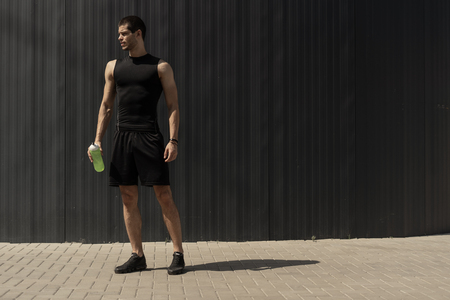 Athletic modern young man posing on a gray metallic wall with a water bottle in his hand. Hydration and nutritions concept. Fitness muscled male. Human mountain power poses. Stock Photo