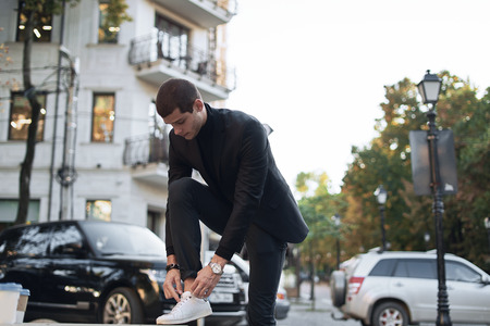 Attractive man stopped on the street to bind laces on his white sneakers. Young fashionable businessman.