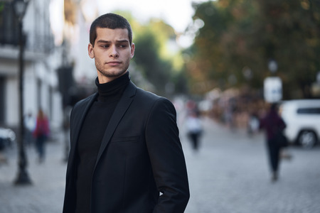 Young man walking, smart casual on an autumn day on a street of European City. Lifestyle Photography