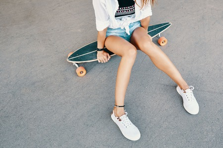 Close up of woman legs in white sneakers on longboard