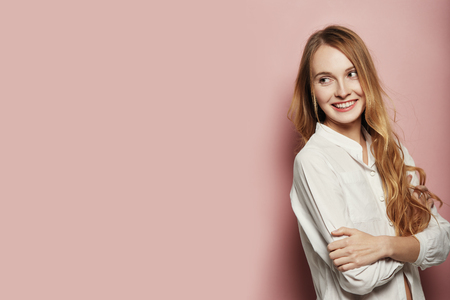 Portrait of pretty Caucasian woman with crossed arms and long hair, wearing a white shirt on pink background Stock Photo