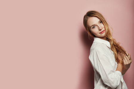 Portrait of pretty Caucasian woman with long hair, wearing a white shirt on pink background Stock Photo