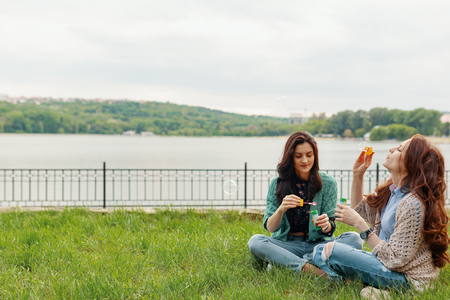 Two sisters having fun while making bubbles and sitting on the grass near the lake with a beautiful landscape in the background Banco de Imagens