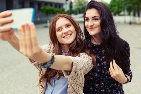Cute pretty girls making funny selfie on the street, having fun together, joy, happiness, love, friendship, sisters. Banco de Imagens