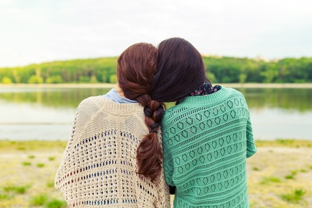 Back view sisters watching beautiful landscape on the horizon with hair braided together. Strong connection concept. 스톡 콘텐츠