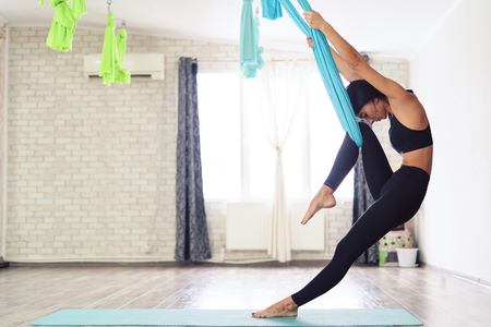 Full length of fit young woman doing antigravity yoga exercises in studio
