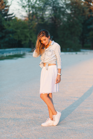 Outdoor portrait of young, beautiful, fashionable smiling girl posing in a stylish, feminine white skirt and sneakers.