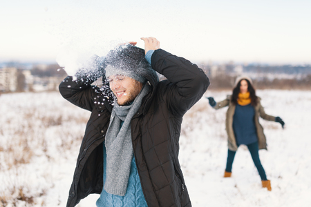 Snowball fight. Winter couple having fun playing in snow outdoors. Young joyful happy young man and woman.