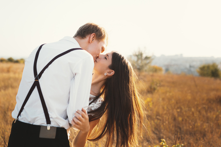 Loving couple dressed in white kissing outdoors, touching, gentle each other with a beautiful landscape in background, golden grass - Concept about people, love and lifestyle