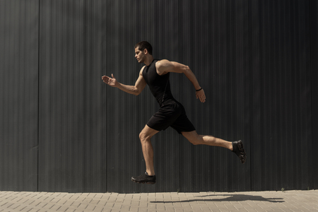 A side view shot of a fit young, athletic man jumping and running. doing cardio interval training against a grey background. Fitness male exercising, outdoors in the morning. Foto de archivo