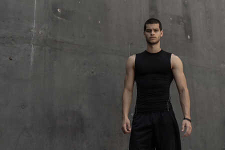 Portrait of athletic muscular young man, in sports clothing, posing on gray industrial background. Fashionable tall male, sport model, muscular body shape, healthy lifestyle advertisment. Foto de archivo