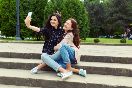 Cute pretty girls making funny selfie on the street, having fun together, joy, happiness, love, friendship, sisters. 스톡 콘텐츠