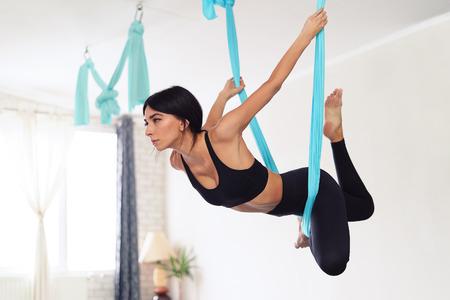 Toute la longueur de la jeune femme en forme faisant des exercices de yoga antigravité en studio Banque d'images