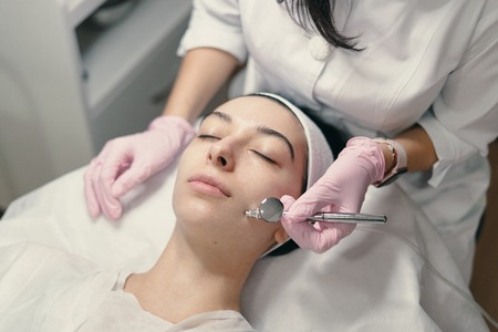 Model with closed eyes and hand's of doctor. Rejuvenating facial treatment. Model getting lifting therapy massage in a beauty SPA salon. Cosmetological clinic, procedure.
