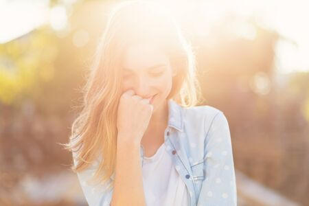 Portrait gorgeous girl with a beautiful smile and attractive facial features on a sunny day with rays reflected on her face. Romantic, fresh, atmospheric people concept. Stockfoto