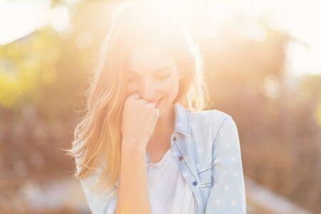 Portret prachtig meisje met een mooie glimlach en aantrekkelijke gelaatstrekken op een zonnige dag met stralen weerspiegeld op haar gezicht. Romantisch, fris, sfeervol mensenconcept. Stockfoto