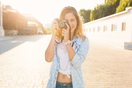 Pretty girl taking photos with a vintage camera on a sunny day, holding it near her eye, smiling. She wears blue sky denim shirt with white big dots and watch. Positive people discover the world.