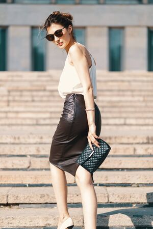 Fashionable brunette businesswoman in a brown leather pencil skirt and cream silk blouse, sunglasses walking in the street, on stairs. Fashion spring, summer photo. Long legs Banque d'images