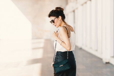 Beautiful smiling young woman in sunglasses wearing leather clutch and skirt, white easy blouse and looking away over the shoulder while walking outdoors. Spirit of the city. Stock Photo