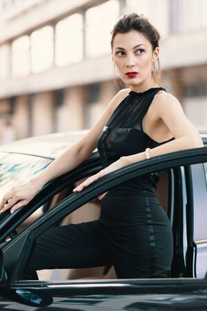 Sensual dangerous woman standing with a feline look in the door of a car wearing a stylish black romper, elegant bun and red lips with a blurred building in perspective. She is ready to win the world.