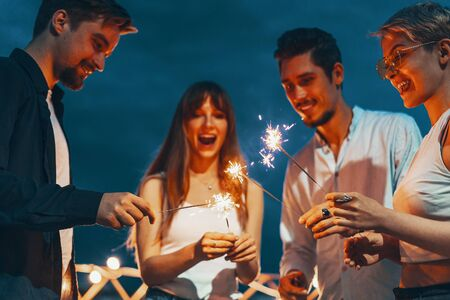 Friends enjoying a rooftop party and dancing with sparklers in hands 写真素材