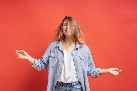 Funny, cute girl having fun isolated on a red background while playing with hair.