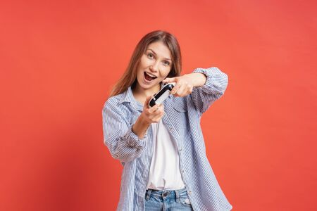 Excited delighted woman playing video games, while holding a game console in hands isolated on red background.