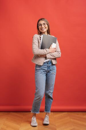 Young smiling student or intern in eyeglasses standing with a folder in hands and happily looking to camera over red background in the studio. 写真素材